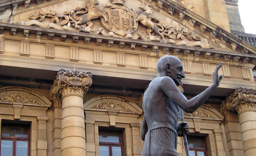 Pietermaritzburg, the capital of KwaZulu-Natal. A contemporary statue of Mahatma Ghandi stands against the heavily ornate facade of the Pietermaritzburg city hall, constructed during British colonial rule.