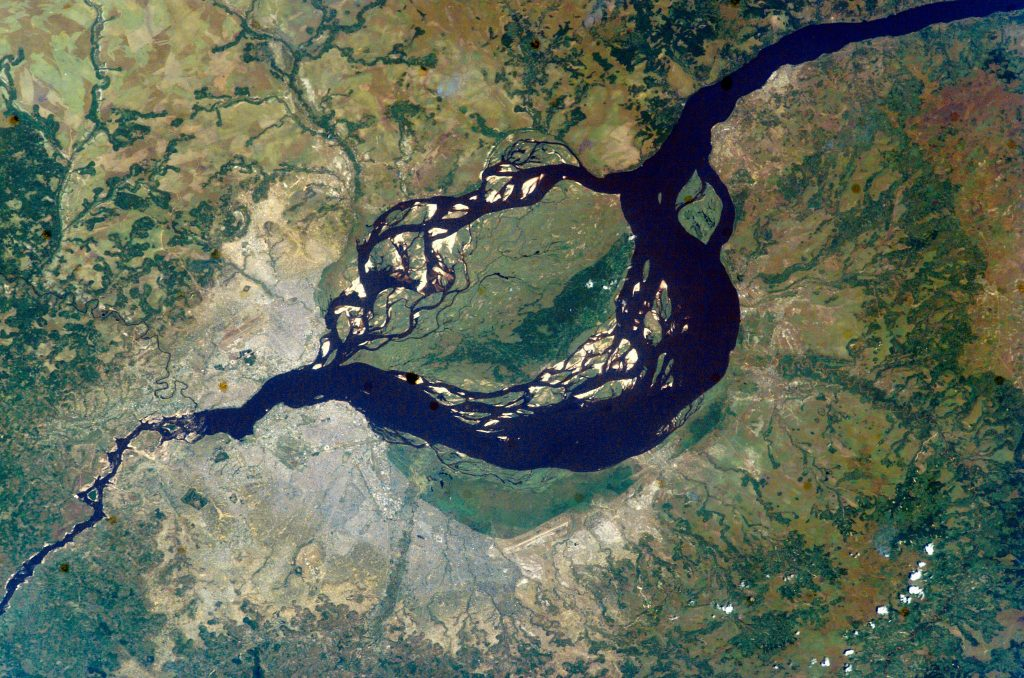 A view of the twin Congo capitals, facing each other across the Congo River. In this 2003 photo taken from the International Space Station, the smaller city of Brazzaville, capital of the Republic of the Congo, is at upper left. The much larger grey area at lower left is Kinshasa, capital of the Democratic Republic of the Congo. The cities lie at the point where the Congo River becomes navigable upstream, widening to the east into Pool Malebo – previously named Stanley Pool by the brutal 19th century British-American explorer Henry Morton Stanley, who prospected the region on behalf of King Leopold II of Belgium.