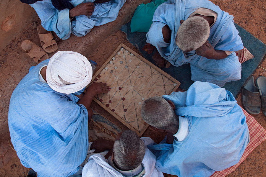 Africa - Men playing the traditional Mauritanian board game of Kharbaga – similar to zamma and draughts – in Ouadane (or Wādān), a small town in the desert region of central Mauritania.