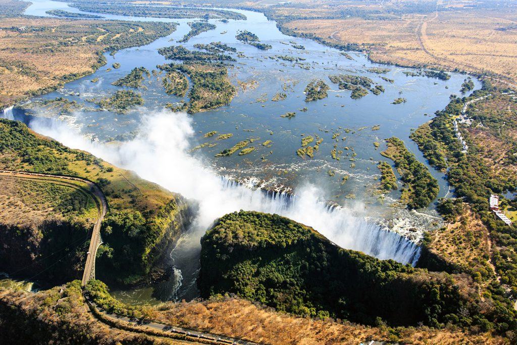 """An aerial view of the massive Zambezi River – which gives Zambia its name – and the Victoria Falls. The waterfall, named Mosi-oa-Tunya or """"the smoke that thunders"""" in Tokaleya Tonga, is said to be the biggest in the world. Its combined width of 1,708 metres and height of 108 metres result in the world's largest sheet of falling water. Here Zambia's border with Zimbabwe runs along the middle of the river, with Zimbabwe on the left and Zambia on the right. The steel Victoria Falls bridge at lower left is a border post between the countries."""