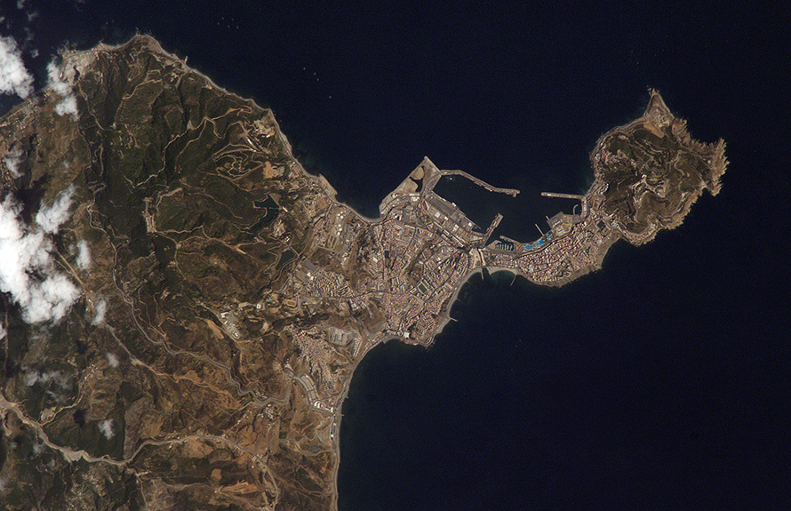Ceuta on the northern African coastline is featured in this image photographed by an Expedition 15 crewmember on the International Space Station. The small Spanish enclave of Ceuta occupies a narrow isthmus of land on the African side of the Strait of Gibraltar. This view illustrates the sharp contrast in land cover between urban Ceuta (pink to white residential and industrial rooftops at center), the bay formed by seawalls to the north of the city, and the higher elevations of Monte Hacho forming the end of the isthmus. Green, vegetated slopes surround the Spanish fort atop the mountain, which commands a clear view of the Strait of Gibraltar to the northwest (not shown). Several small dots are visible near the coastline to the northwest and south of Ceuta -- these are small pleasure or fishing boats.
