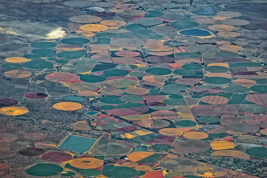 An aerial view of circular crop fields watered by centre-pivot irrigation systems near the small farming town of Jacobsdal in the eastern Free State, near the Northern Cape border. (Jean Boris Hamon, CC BY-NC-ND)