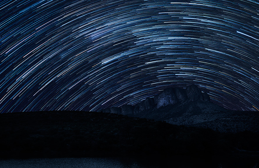 Star trails curve over the massif of the Waterberg Mountains in a time-lapse night shot taken from the Tlopi Tented Camp in Marakele National Park, Limpopo province. The surface of Tlopi Dam can be seen in the foreground. (Martin Heigan, CC BY-NC-ND 2.10) Martin Heigan mh@icon.co.za http:\anti-matter-3d.com http:\www.flickr.comphotosmartin_heigan