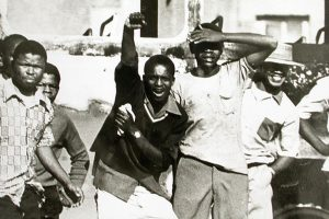 Young men taunt police photographers in Soweto in June 1976. (Doing Violence to Memory: The Soweto Uprising)