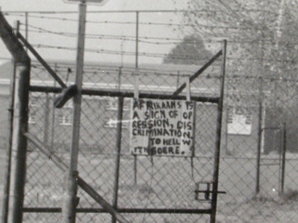 "A student's poster on a fenced-in Soweto school reads: ""Afrikaans is a sign of oppression, discrimination. To hell with Boere."" (Doing Violence to Memory: The Soweto Uprising)"