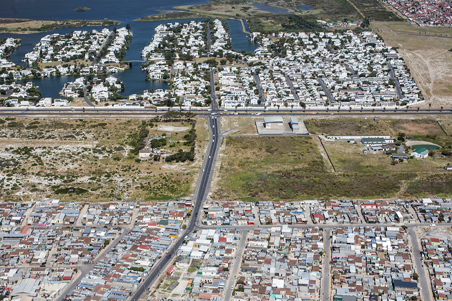 <em>An area of Muizenberg, Cape Town. In the foreground, the shacks and low-cost houses of Vrygrond township. In the background, the luxury homes of the Marina da Gama secure housing complex. South Africa has one of the highest levels of inequality in the world. (Mikael Colville-Andersen, CC BY 2.0)